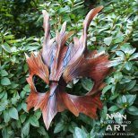 Photo of a leather mask with leaf shaped carvings