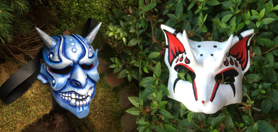 image showing two masks. One mask is a blue resin oni mask the other is a white red and black cat mask