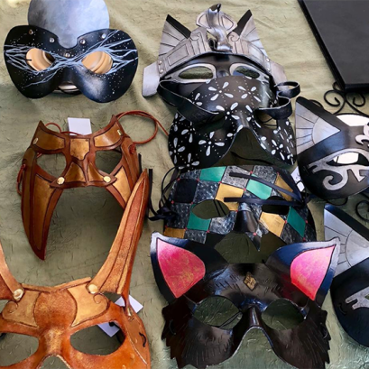 several leather carnival masks on a table